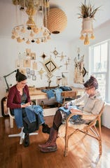 Melanie Falick, left, embroiders on a pair of her jeans in the studio of another hand-sewer.