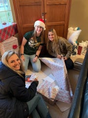 "Michigan pitcher and die-hard ""Star Wars"" fan Meghan Beaubien wraps presents for Big Brothers Big Sisters of Washtenaw County."