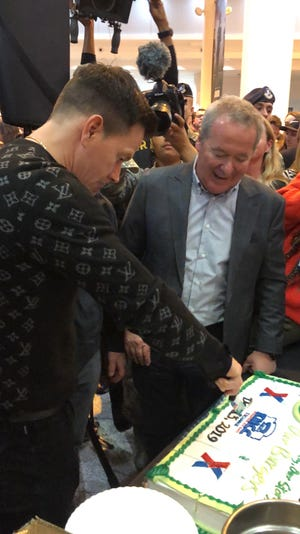 Actor Mark Wahlberg, left, and Wahlburgers partner, Nino Cutraro cut the cake in Germany