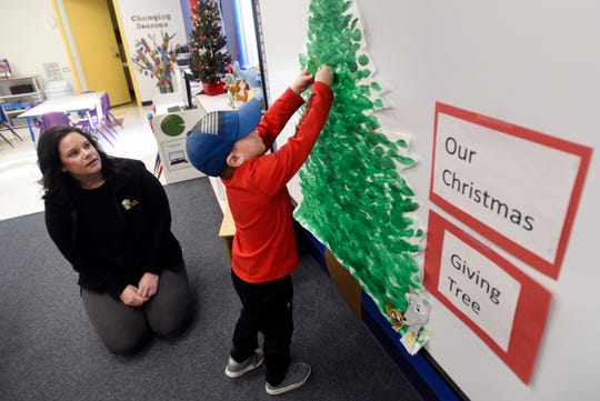 The Learning Experience teacher Sam Fulkerson watches as student Colin Christofferson hangs up an idea written on a paper ornament on the classroom's giving tree, Dec. 16 in South Lyon. Fulkerson asked her students for ideas of kind things one can give a person.