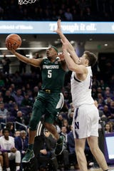 Michigan State guard Cassius Winston, left, drives to the basket against Northwestern center Ryan Young during the first half.