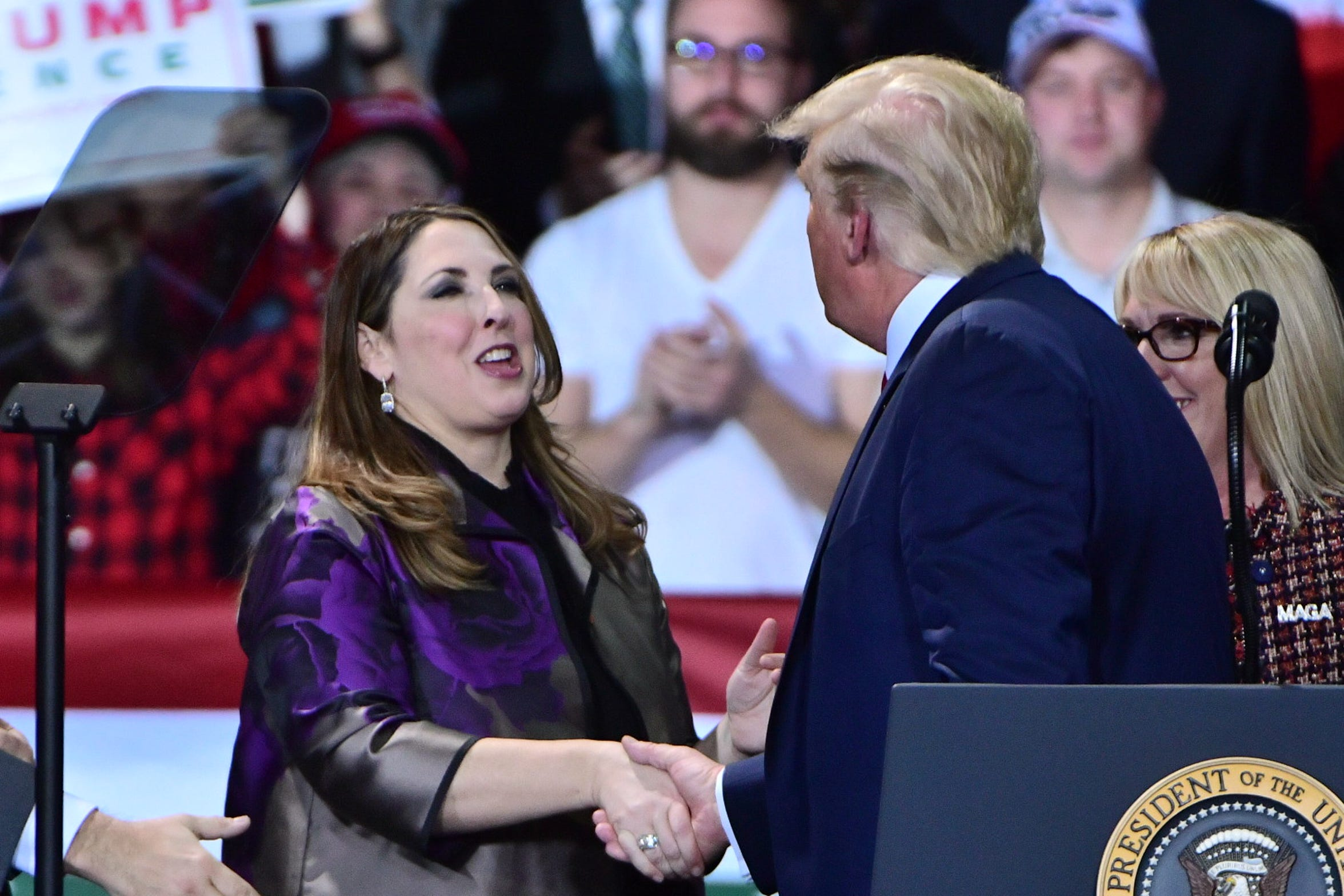 Ronna McDaniel, Chair of the Republican National Committee, shakes hands briefly with President Donald Trump after he invited her on stage during a political rally in Battle Creek.