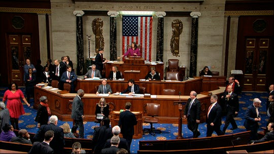 Members walk on the floor as voting begins in the House of Representatives in the first article of impeachment against President Donald Trump at the Capitol in Washington, Wednesday, Dec. 18, 2019.