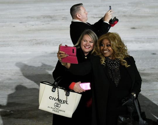"Michigan supporters, from left, Meshawn Maddock, national advisory board member of Women for Trump, and Linda Lee Tarver, national advisory board member of Black Voices for Trump, take a photo, as does Andrew ""Rocky"" Raczkowski, in background, national advisory board member of Veterans for Trump, as Air Force One arrives at Battle Creek Executive Airport at Kellogg Field in Battle Creek."