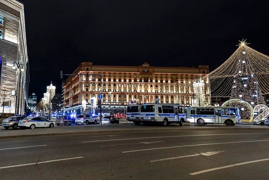 Police buses and cars block the area near the building of the Federal Security Service (FSB, Soviet KGB successor), right, in the background in Moscow, Russia, Thursday, Dec. 19, 2019. Russia's main security agency says shots have been fired near its headquarters in downtown Moscow.