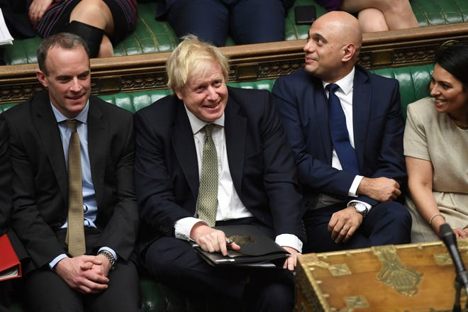 In this photo made available by the UK Parliament, Britain's Prime Minister Boris Johnson, center, attends the debate in the House of Commons, London, Thursday Dec. 19, 2019.