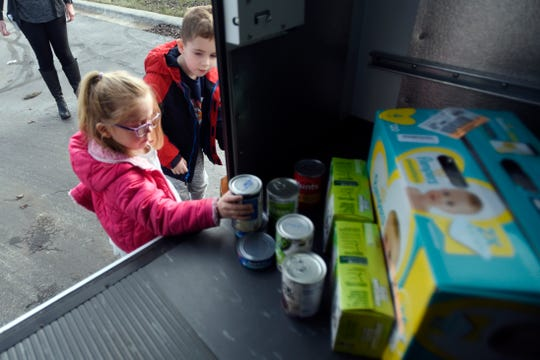 Kate Meldrum, a student at The Learning Experience, loads canned good donations onto a bus. The donations will be taken to Lacasa, a nonprofit that helps victims of abuse, based in Howell.