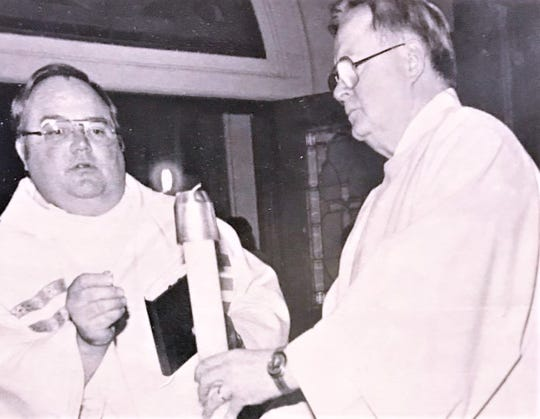 Deacon Stanley Douglas, right, takes part in a service at St. Mary's Church in Elmira with then Pastor Jim Boyle.