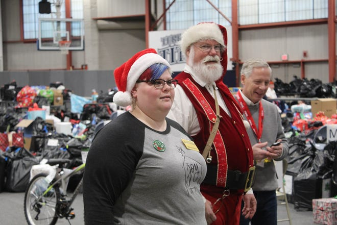 Mandy Burris and John Havens, in Santa suit, greet guests as they come in for the annual Community Christmas.