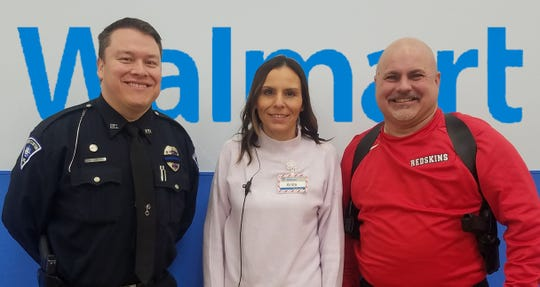 Port Clinton Police Officer Mark Anderson, left; Port Clinton Walmart Supercenter Store Manager Anita Merritt, center, and Port Clinton School Resource and Attendance Officer Richard Vance accepting a donation to PCPD.