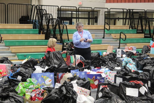 Workers sort through hundreds of bags of toys given out during the county's annual Community Christmas.