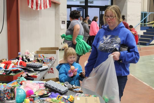 Crystal Woessner and daughter Abygail O'Brein, 4, pick out extra gifts from a table at Sandusky County Community Christmas Wednesday.