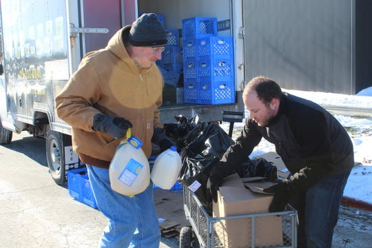 Joshua Kensler, right and Jim Faist, left, load up a cart with milk and a turkey as part of Sandusky County Community Christmas.