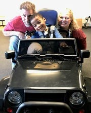 Elijah Walker smiles with his parents in his new car, gifted by his physical therapist at Colorado in Motion in Fort Collins on Dec. 14.