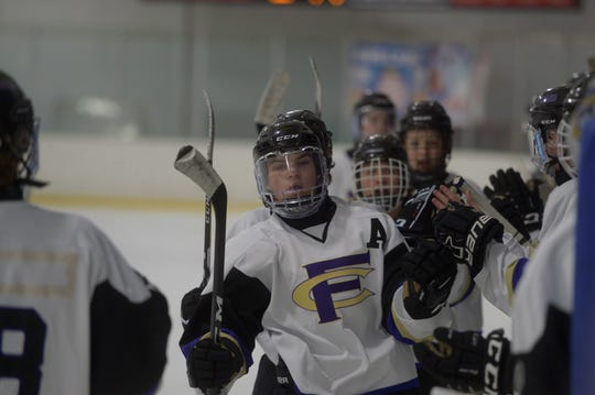 Fort Collins hockey player Noah Williamson, front, is high-fived after scoring during a game against Dakota Ridge at NoCo Ice Center on Thursday, Dec. 19, 2019. The No. 4 Lambkins won 6-3.