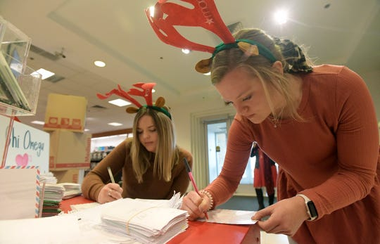 Libby Sanford, right, and Alex Verosky, both members of the University of Wyoming Chi Omega sorority, fill out letters to Santa after they delivered over 75,000 letters to Santa from their chapter to Macy's in Fort Collins, Colo. on Thursday, Dec. 19, 2019. Macy's will donate $1 to Make-A-Wish for every letter donated.
