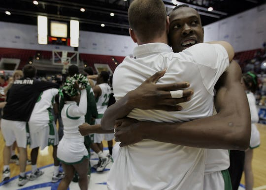 Fort Myers center Josue Celestin celebrates with coach Scott Guttery after beating Oak Ridge to win the Class 4A state basketball championship at the Lakeland Center on Saturday March 6, 2010.