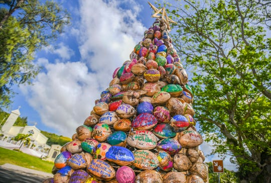 Hundreds of hand-painted coconuts, arranged in the form of a Christmas tree, greet passing motorists, near the San Dimas Catholic Church and the old bell tower in the southern village of Merizo, on Thursday, Dec. 19, 2019. The tropical seeds were decorated by the village residents and others with people's names, personal messages, island church parishes, artwork and holiday wishes.