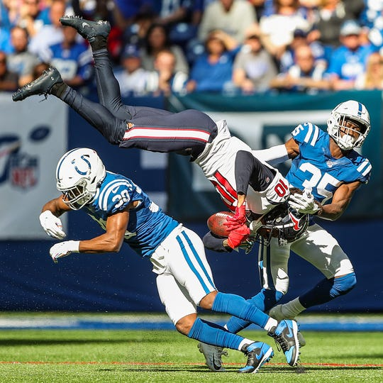 Houston Texans wide receiver DeAndre Hopkins (10) leaps between Indianapolis Colts defensive back George Odum (30) and cornerback Pierre Desir (35) during the second quarter of their game Lucas Oil Stadium in Indianapolis in NFL Week 7, Sunday, Oct. 20, 2019.
