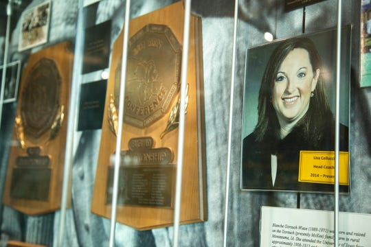 Big Ten Conference field hockey trophies are displayed in an exhibit alongside a photo of current field hockey coach Lisa Cellucci, Wednesday, Dec. 18, 2019, at University of Iowa Athletics Hall of Fame in Iowa City, Iowa.
