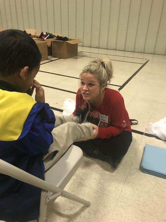 Regions Bank Branch Manager Holly Dean talks with an Andrew Jackson Elementary student before getting his new shoes for him.