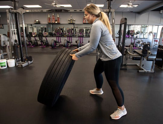 Abbie Bayless, seen here flipping tires at New Body Fitness in Milan, does 45 minutes of high-intensity interval training three times a week.