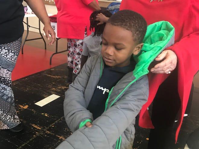 Bank of Jackson's Anita Kay Archer helps Zy'Kavion Cox Bond try on a new coat at Washington-Douglass Head Start/Early Head Start on Wednesday.