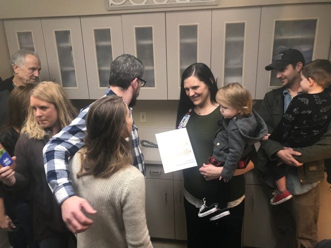 Addy Grisham holds her daughter, Mila, while she and her husband, Brian, talk with family moments after the unveiling of the new family bereavement room in the emergency department of Jackson-Madison County General Hospital on Wednesday.