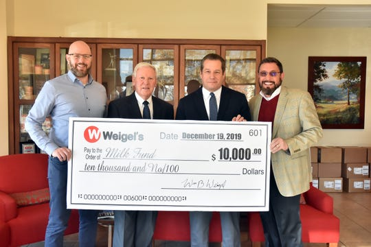 Knox News executive editor Joel Christopher (left) and President Frank Rosamond (right) accept a check for $10,000 for the Milk Fund from Weigel's CEO Ken McMullen and Weigel's president Doug Yawberry on Thursday, Dec. 19, 2019.