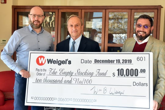 Weigel's chairman Bill Weigel, center, donated $10,000 to the Empty Stocking Fund and accepting the check are executive editor Joel Christopher, left, and president Frank Rosamond.