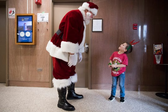 Blount County Mayor Ed Mitchell, dressed as Santa, greets Camryn Sayne, 4, of Maryville, outside his office after exiting an elevator Tuesday, Dec. 3, 2019. Mitchell has played Santa for over a decade.