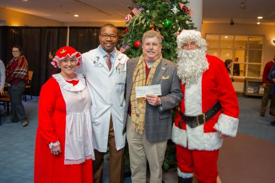 Dr. Keith Gray, UT Medical Center's senior vice president and chief medical officer, hands a check to Foster Arnett, representing the News Sentinel's Empty Stocking Fund. Santa and Mrs. Claus were around for the festivities.