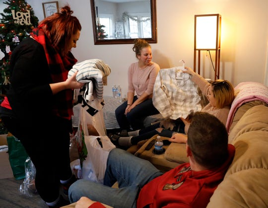 Fel Mason, 16, holds up a pair of pajamas she received from as part of Fairfield County Job and Family Service's annual gift drive for their foster care clients. Fel was adopted by Heather, second from left, and Cory Mason earlier this year. At right is the family JFS case worker Katrina Shaffalo.