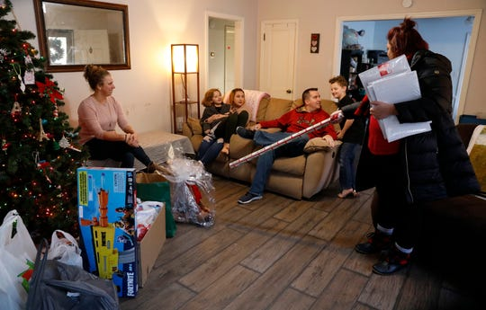 Fairfield County Job and Family Services caseworker Katrina Shaffalo uses a roll of wrapping paper to point out a Nerf Fortnite gun to Andrew Mason, 7, second from right, Wednesday, Dec. 19, 2019, the Mason family's home in Lancaster. Shaffalo was the family's caseworker as Heather, left, and Cory Mason, third from right, adopted Fel Mason, 16, third from left, holding Alexis Mason, 9.