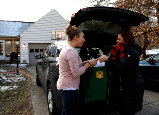 Heather Mason, left, reacts as she realizes how many Christmas gifts donors purchased for the family as Katrina Shaffalo hands her one of my bags. Shaffalo is the Mason family's Fairfield County Job and Family Services casework. Heather and her husband Cory Mason adopted a teenage girl earlier this year.