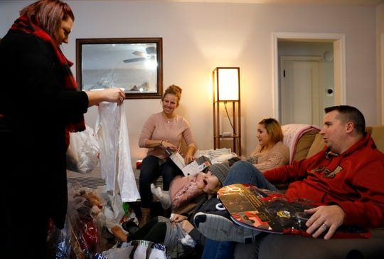 Alexis  Mason, 9, center, reacts as she see a T-shirt Katrina Shaffalo, left, a case worker with Fairfield County Job and Family Services, is holding up for her. Shaffalo brought the Mason family Christmas presents purchased by an anonymous donor for the entire family. Donors purchase gifts for the agencies foster care families. Heather Mason, second from left, and Cory Mason, right, adopted Fel Mason, 16, second from right earlier this year.