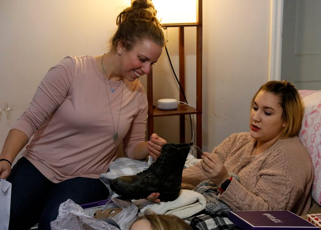 Heather Mason, left, looks at a pair of boots her daughter Fel Mason, 16, received as a Christmas present Wednesday, Dec. 19, 2019, at their home in Lancaster. Fel was adopted by Heather and Cory Mason earlier this year. The family received Christmas presents through a donation program with Fairfield County Job and Family Services.