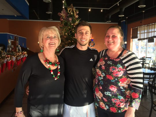 George's Restaurant server Jenny Rideout, left, new owner Robert Domgjoni and Manager Heather Thierry stand by a Christmas tree in the eatery, Thursday, Dec. 19, 2019.