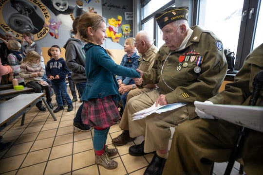 94 year-old George Merz, veteran of the Battle of the Bulge is greeted by a young student at the Noeville Belgium Public School. Dec. 13, 2019