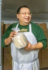 Juan Holguin, employee of La India Tortilleria in Mason, Michigan, shows some tamales prepared for local customers and restaurants on Thursday, Dec.19, 2019.