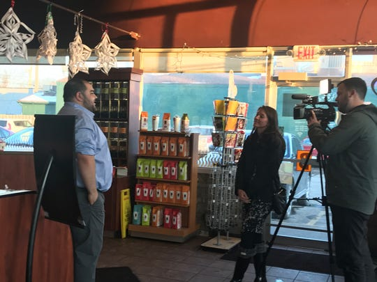 Hatim Shetiah talks to a news crew Dec. 19, 2019 about the closing of the original Biggby's in East Lansing, now owned by his family. The franchise will reopen at 300 Grand apartments in early January.