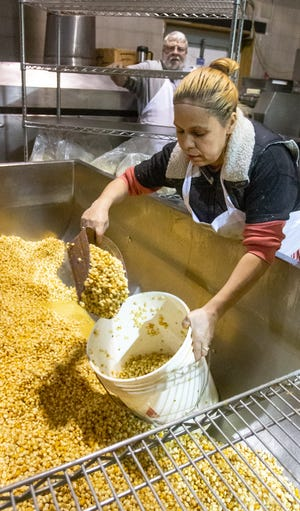 Silvia Gonzalez Lopez, employee of La India Tortilleria and owner of Taquero Mucho food truck, loads fresh corn to be ground into masa for customers and restaurants with George Helbig, in back, at the factory in Mason, Michigan on Thursday, Dec.19, 2019.