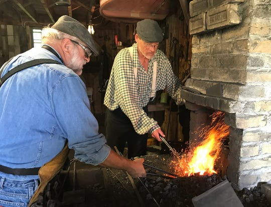 Blacksmiths George Baldwin of Kewaunee, Wis., and George Wendt of Campbellsport, Wis., work on heating pieces of metal at the Blacksmith Shop at Pinecrest Historical Village, Saturday, August 10, 2019, in Manitowoc, Wis.  The village will repeat the activities on Sunday.