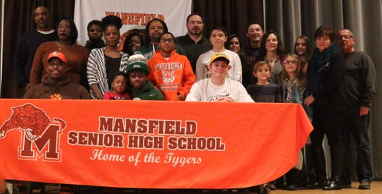 The families of Clay Caudill, Angelo Grose and Anthony Hawkins join them on stage for a photo during their signing day on Wednesday evening.
