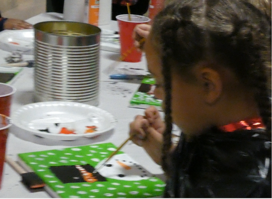 Aliyah Grose, 7, paints a snowman on canvas Thursday night at Friendly House during the annual Mansfield Kiwanis Club Christmas party.