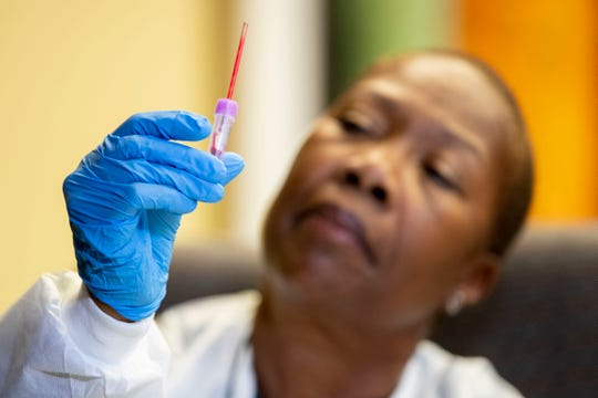 Registered nurse Cornelia Bobo checks the level of a blood sample while demonstrating a lead poisoning test Thursday, Dec. 19, 2019, at the Shelby County Health Department in Memphis.