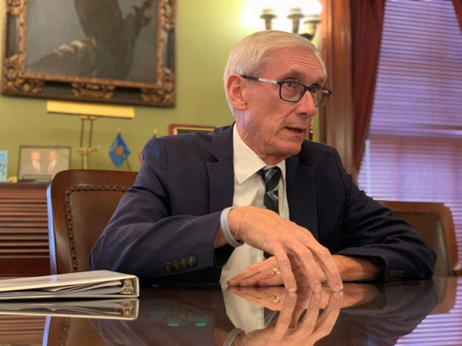 Gov. Tony Evers speaks to reporters in his office at the Wisconsin State Capitol in December 2019.