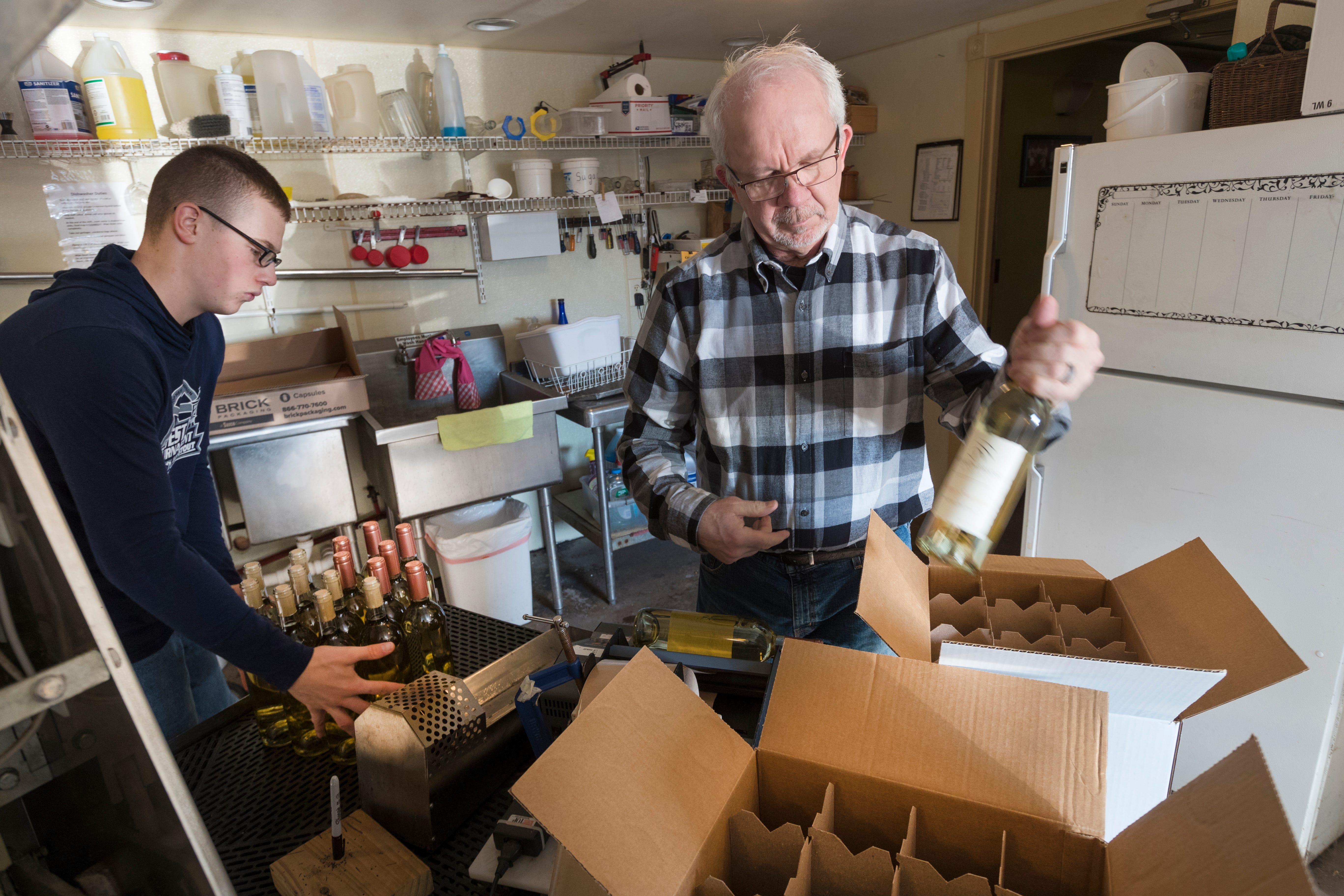 Tom Rohland fills cases of wine with the help of Isaac Mathison, left, at Munson Bridge Winery in Withee. Former dairy farmers Tom and Sheri Rohland own the winery.