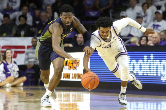 Marquette freshman guard Symir Torrence goes after the ball against Kansas State guard David Sloan.