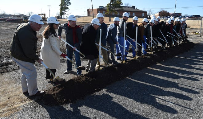 Baxter Regional Medical Center officials, physicians and others line up to ceremonially break ground Wednesday on the hospital's outpatient surgery center. The 23,000 square-foot facility should be open in early 2021.